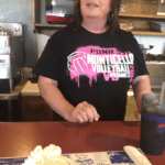 Woman posing with a piece of pie at her cafe