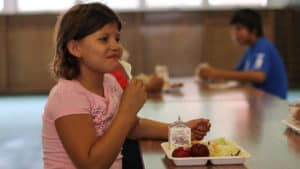 A girl smiles while eating a meal at Eagle Butte, South Dakota.